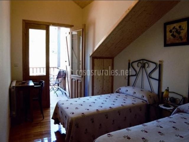 Dormitorio con camas individuales y terraza