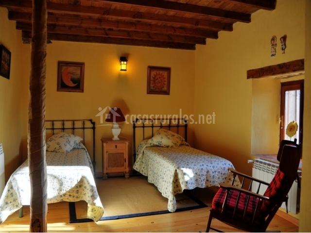 Dormitorio con dos camas individuales y mecedora delante