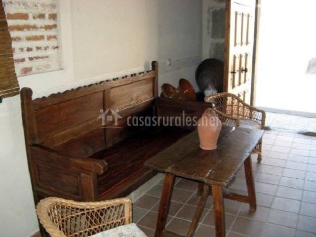 Banco de madera con sillas de mimbre a los lados en el patio