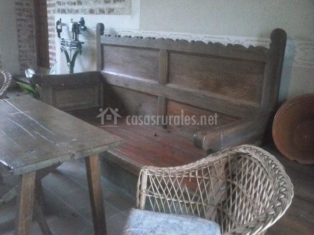 Banco de madera junto a mesa y una silla de mimbre