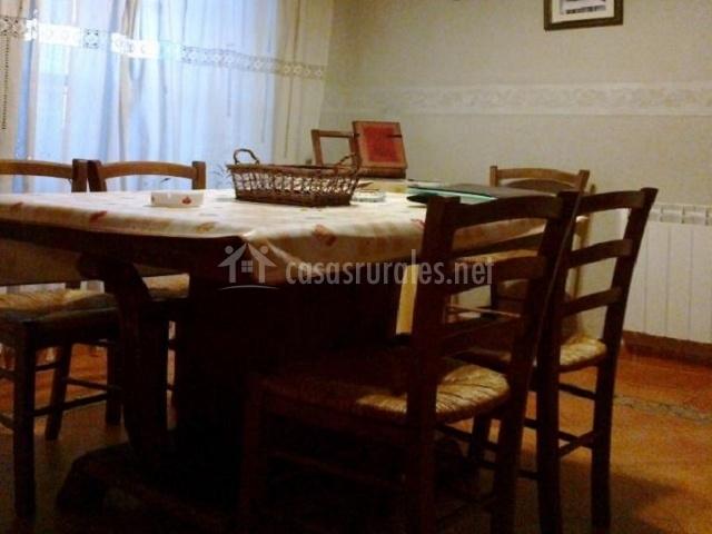Comedor con mesa de madera y sillas y cuadros colgados