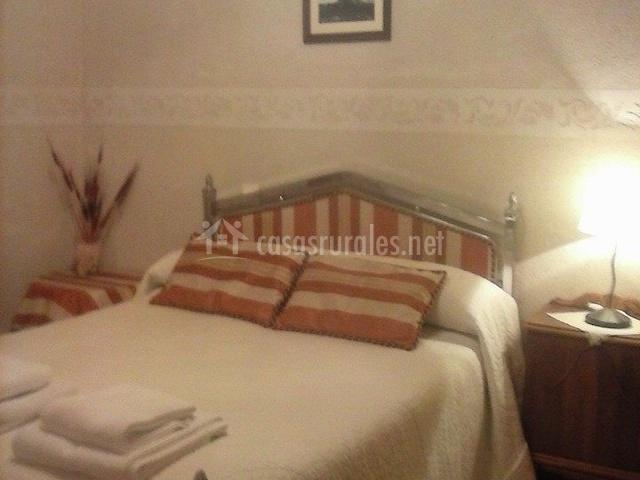 Dormitorio con cama de matrimonio y lamparilla encendida