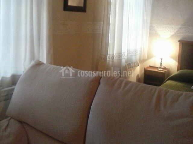 Dormitorio con cama verde y sillón delante