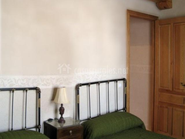 Dormitorio doble con dos camas con cabecero de barras