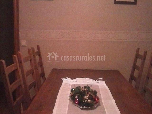 Mesa de comedor con sillas de madera y centro de mesa