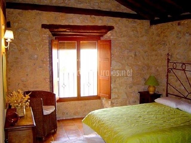 Dormitorio con cama verde de matrimonio y butaca individual