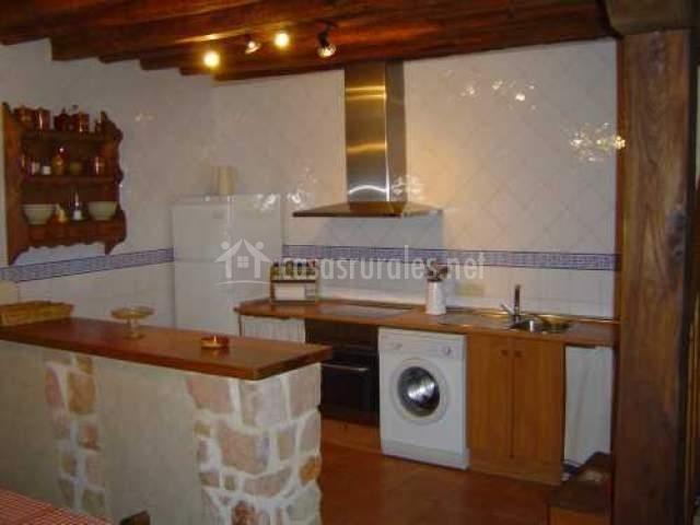 Entrada a la cocina con barra americana de piedra