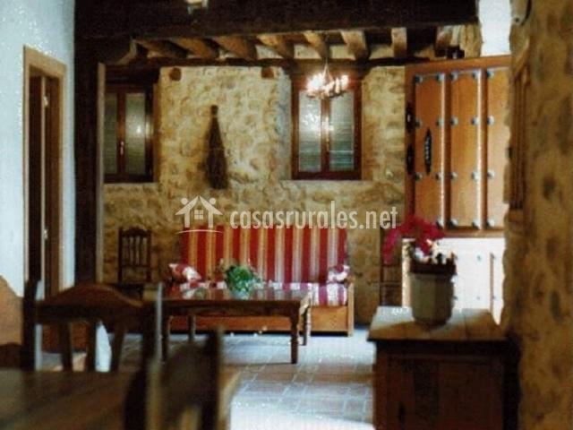 Salón comedor con paredes de piedra y mesa de madera