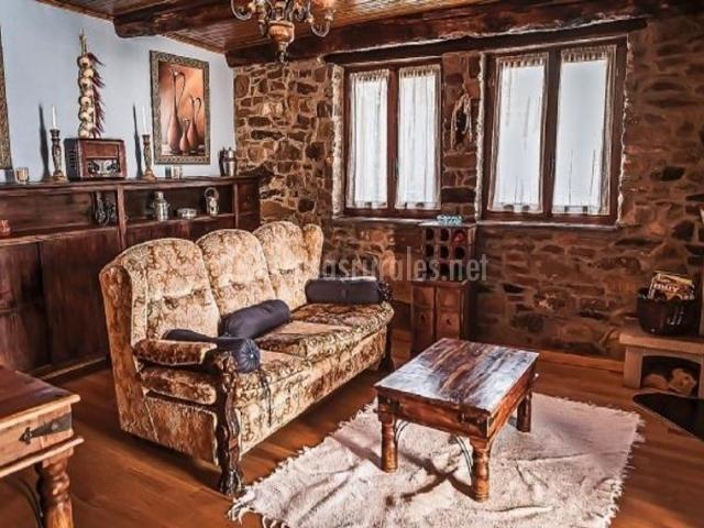 Sala de estar con paredes de piedra que dejan ver las ventanas