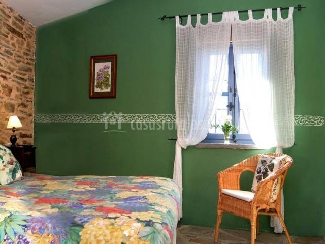 Dormitorio verde con ventana y silla de mimbre