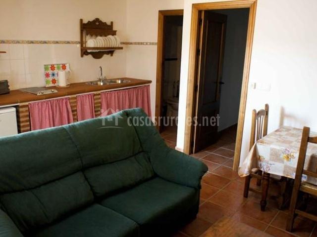 Sofá verde con cocina detrás