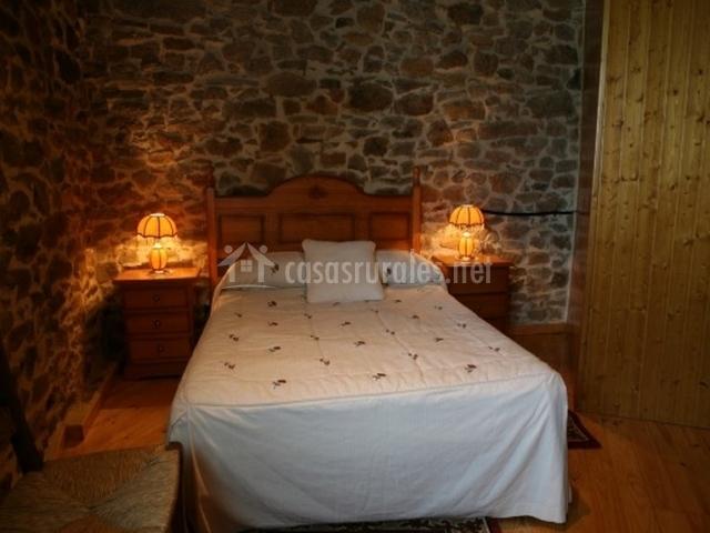Cama de matrimonio en dormitorio con paredes de piedra