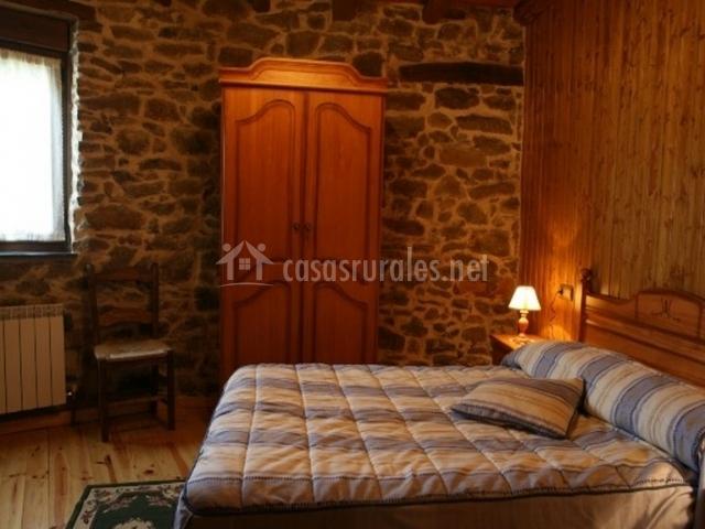 Dormitorio con cama de matrimonio y pared de piedra de la casa rural