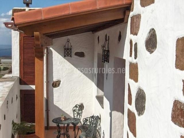 Vistas del porche de la casa con mesa y sillas de forja
