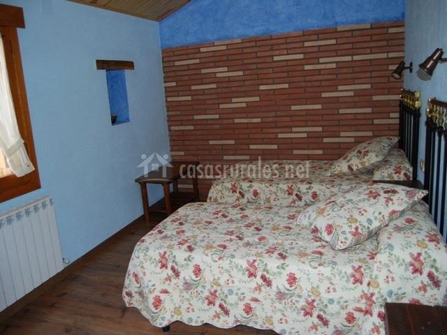 Dormitorio en azul con pared de ladrillo visto