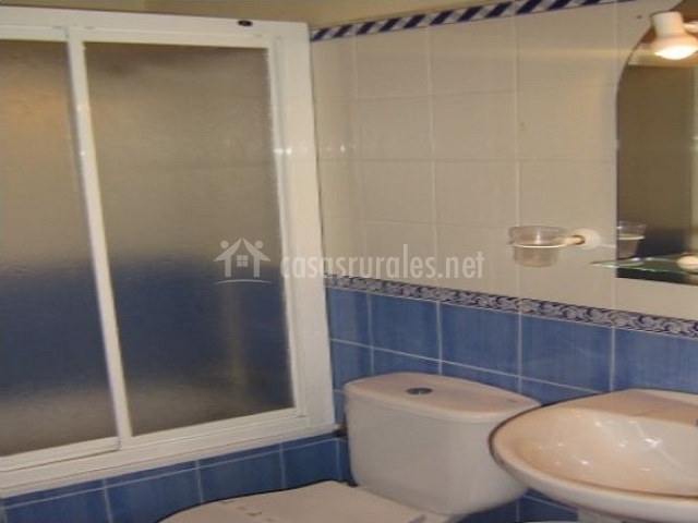 Baño con azulejos azules y blancos y bañera