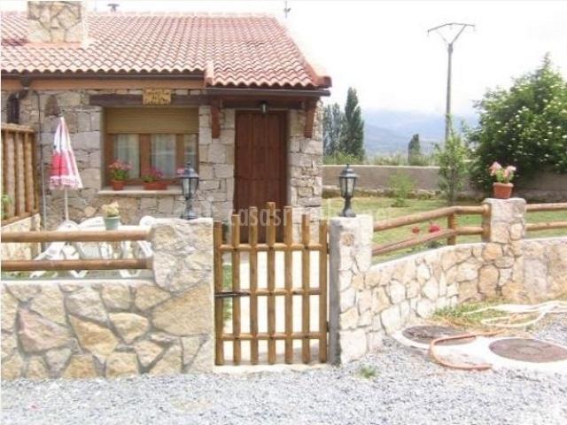 Entrada a la casa rural con valla de piedra y mesa con sombrilla roja y blanca a la entrada