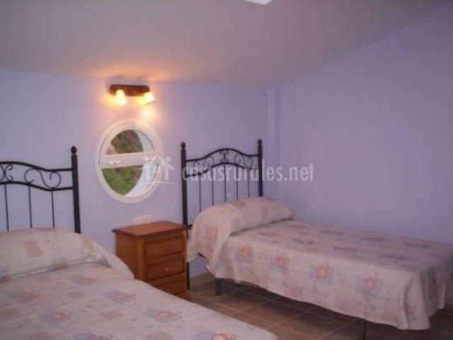 Dormitorio con dos camas individuales y ventana redonda
