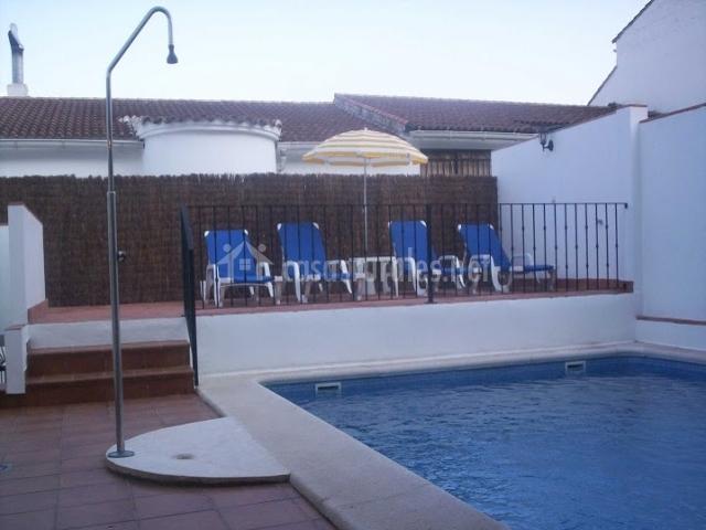 Piscina con ducha y zona de tumbonas al lado