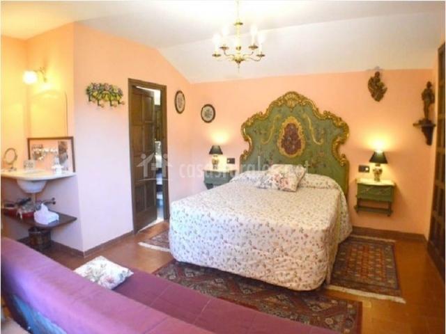 Dormitorio doble con baño privado completo y lavabo en la entrada. Dispone de sofá y amplios armarios