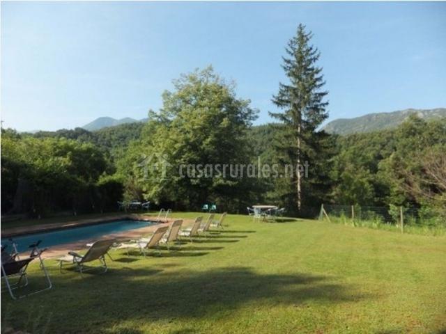 Jardín con piscina y zona de hamacas