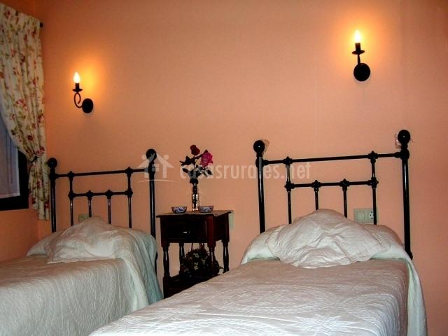 Dormitorio doble con dos camas individuales y visillos con flores