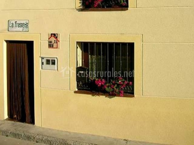 Entrada a la casa con ventana con flores y barrotes
