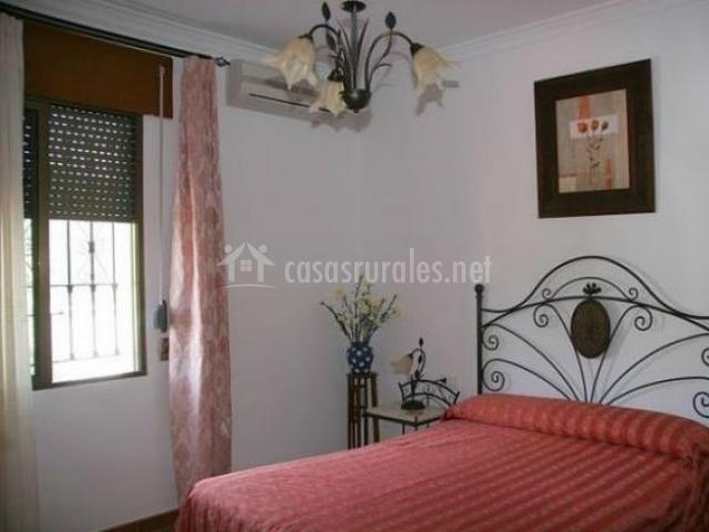 Habitación con cama de matrimonio y colcha roja