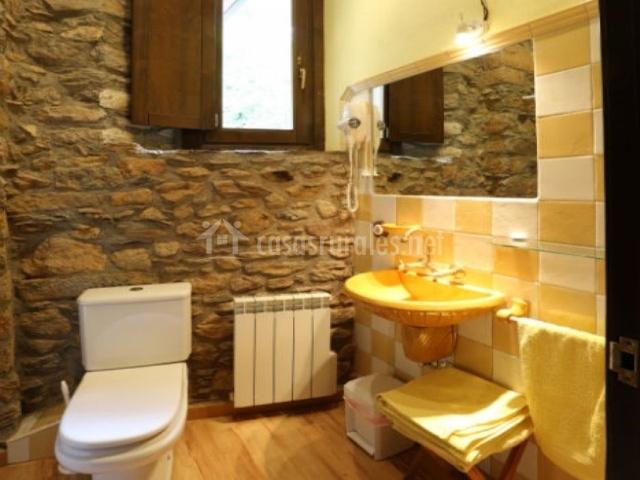 Cuarto de baño amarillo con pared de peidra