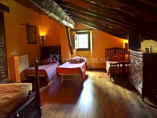 Dormitorio con cuatro camas y techo abuhardillado