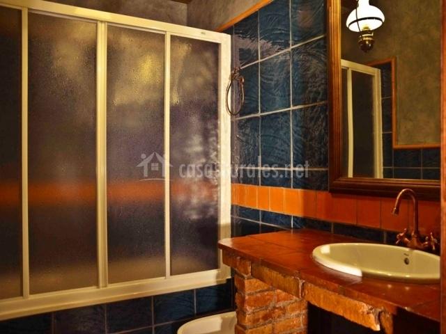 Servicio con azulejos azules y mueble lavabo
