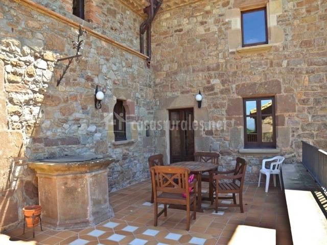 Terraza con mobiliario y pared de piedra
