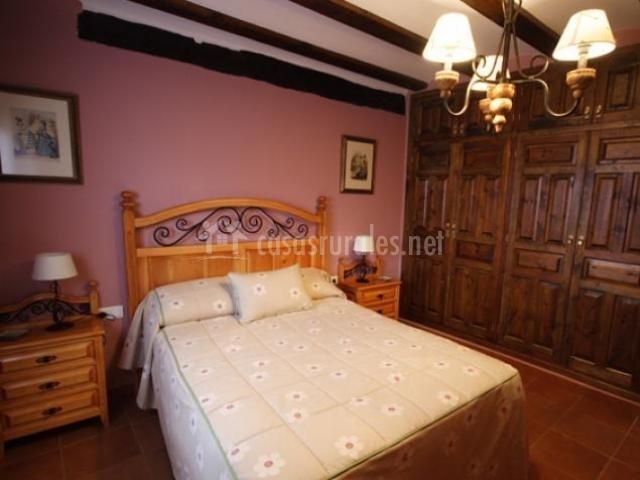 Habitación con cama de matrimonio y armario empotrado de madera