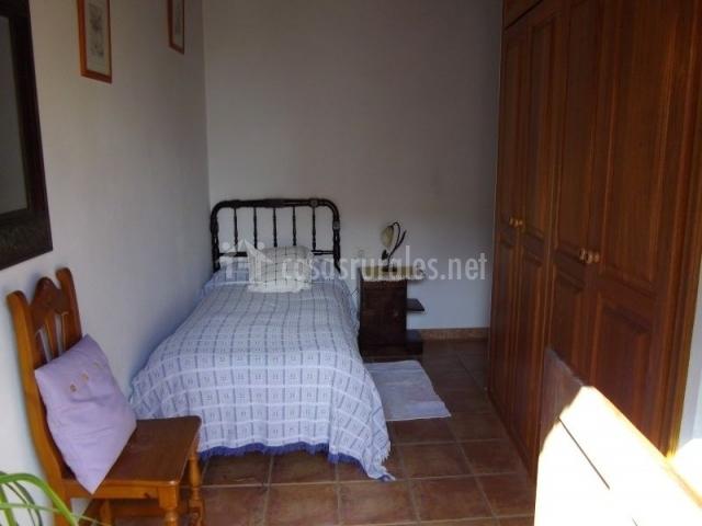 Dormitorio con armario de madera y cama individual