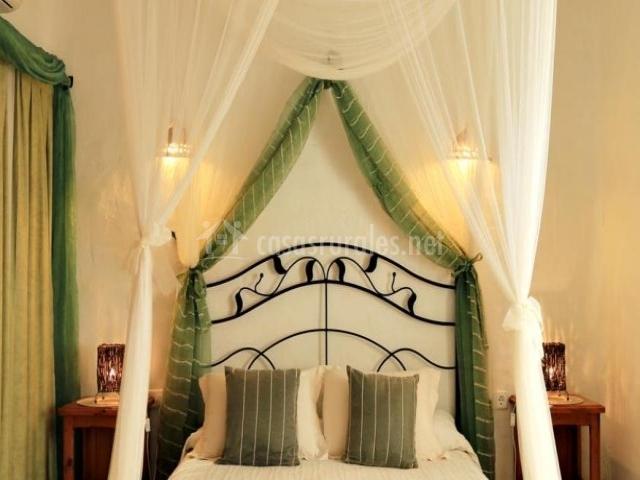 Dormitorio de matrimonio con dosel en la cama