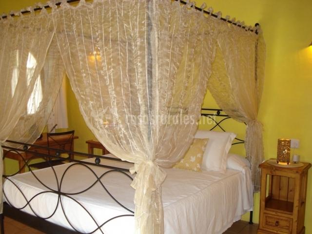 Dormitorio de paredes amarillas con dosel en la cama