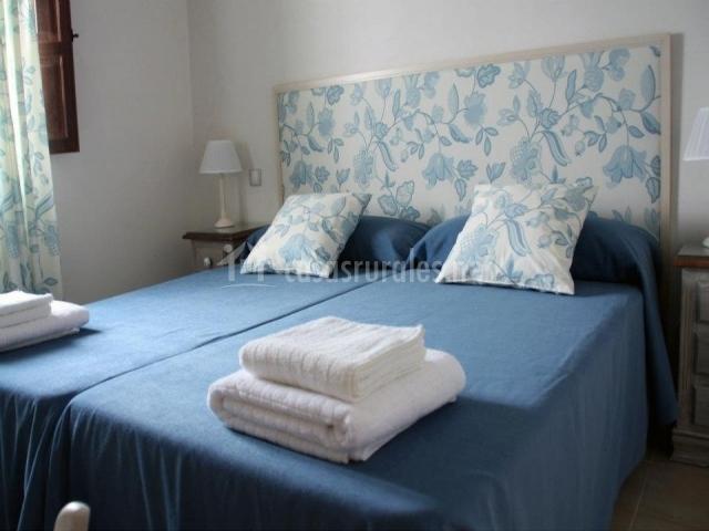 Dormitorio azul con cabecero de tela