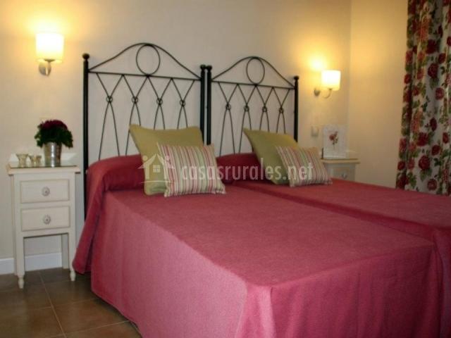 Dormitorio doble con cabeceros forjados y sabanas rosas
