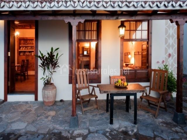 Terraza de la vivienda con mesita y porche cubierto