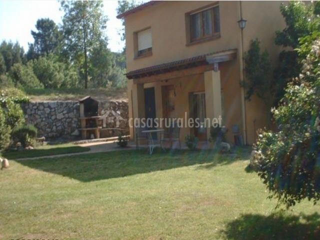 Exterior de la casa rural con barbacoa y muebles de jardin
