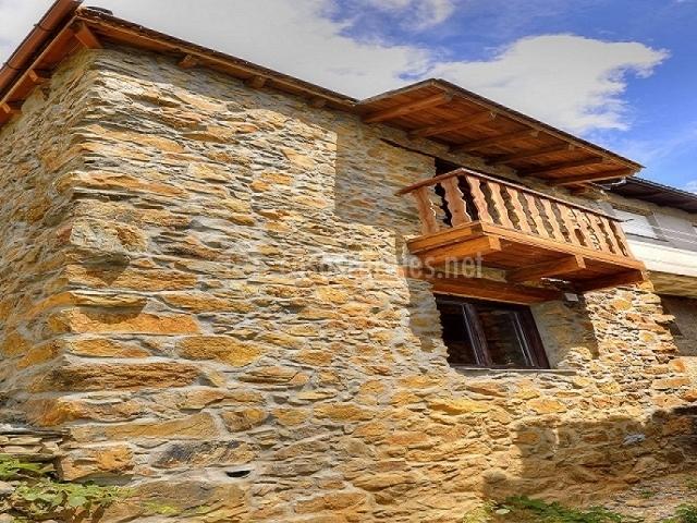 Fachada de la casa, de piedra, con balcón de madera