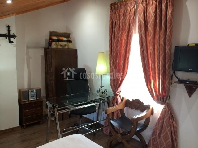 Dormitorio abuhardillado con escritorio y televisor