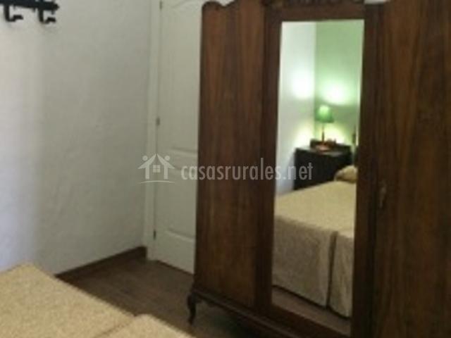 Dormitorio con dos camas y armario con espejo
