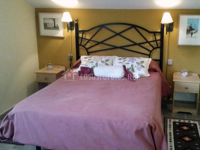 Dormitorio con cama de matrimonio y cabecero de forja
