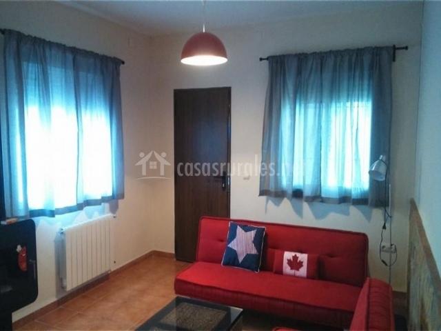 Sala de estar con sofá cama y ventanas