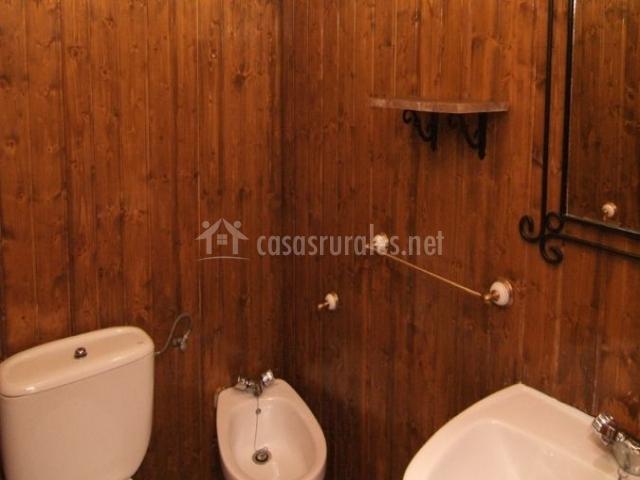 Aseo con paredes de madera y sanitarios