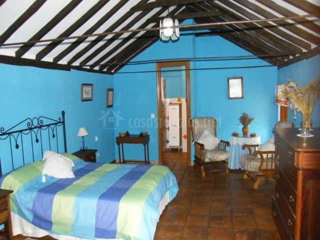 Dormitorio de matrimonio en azul con su aseo
