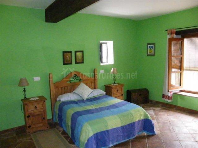 Dormitorio de matrimonio verde con amplios espacios luminosos