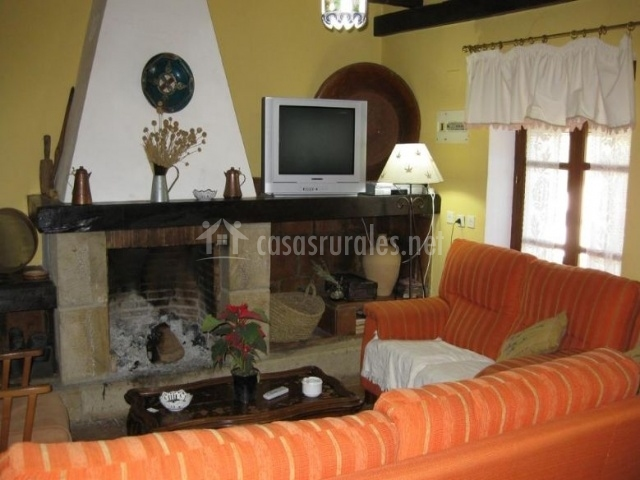 Sala de estar con chimenea y sillones en naranja