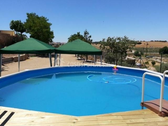 Vistas de la piscina en el exterior con sombrillas